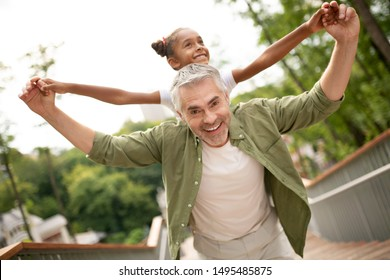 Playing with daughter. Happy grey-haired man feeling amazing playing with foster daughter