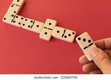 Playing dominoes on a red background . Man's hand with a Domino.