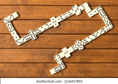 Playing dominoes on a wooden table. The view from the top. Dominoes game concept.