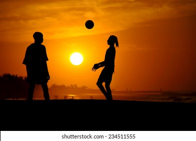 Playing football at the sunset on the beach