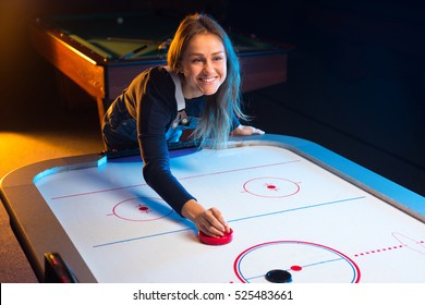 Playing a game of air hockey in the game room