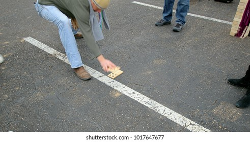 Playing a game of dominos in a parking lot. Large wooden dominos used for playing outdoors.