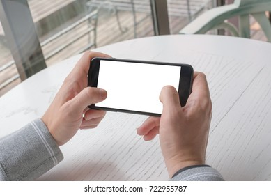 Playing game on smart phone. Closeup view. Mobile phone with isolated screen for app promotion. Horizontal position.