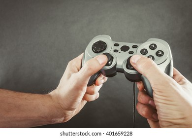 Playing games concept. Part body man with joystick play game on console. Male hands holding grey pad.