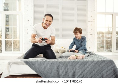 Playing games. Handsome exuberant well-built father smiling and playing games with his son and they holding remote controls