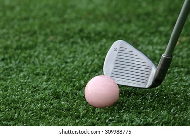 Playing golf with a pink golf ball