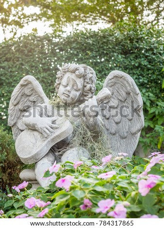 Playing Guitar Little Angel Statue In Outdoor Garden Under Evening Light