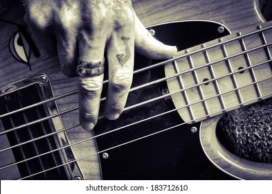 Playing guitar. Tattooed fingers playing bass.