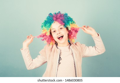 Playing with her hair. Funny kid with curly synthetic hair. Cute little girl with fancy hair. Adorable small child wearing bright clown hair wig.