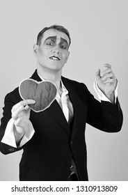 Playing love. Mime man hold red heart for valentines day. Love confession on valentines day. Mime actor with love symbol. Theatre actor pantomime falling in love.