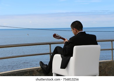 Playing the mandolin by the ocean