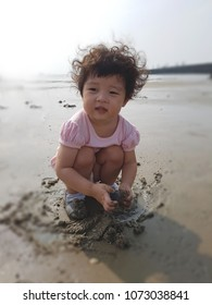 Playing muddy little girl in the tideland at the seashore
