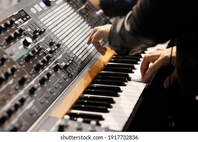 Playing music on the keyboard of a modern analog synthesizer. Selective focus.