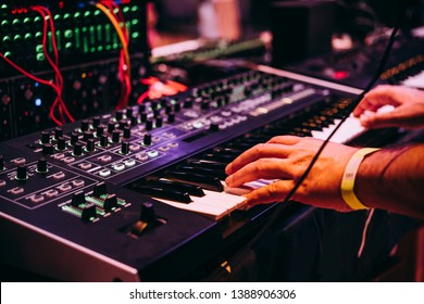 Playing music using an analog synthesizer connected to a modular synthesizer. Electronic music and professional music equipment concept.