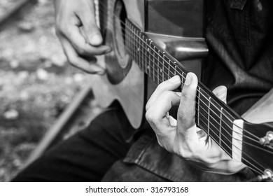 Playing on acoustic guitar. Close-up., Black and white photo