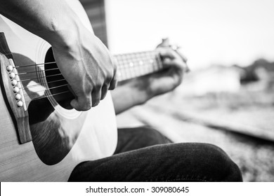 Playing on acoustic guitar outdoor. Black and white photo