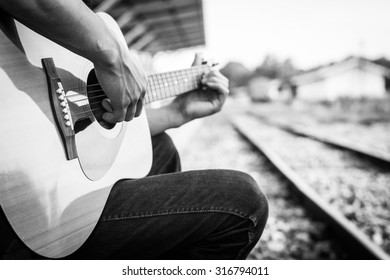Playing on acoustic guitar outdoor, Black and white photo