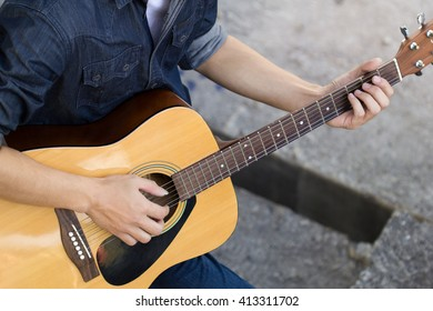 Playing on acoustic guitar outdoor