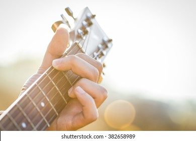 Playing on acoustic guitar outdoor,closeup