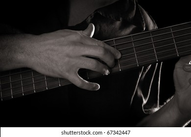 playing on six-string electric bass guitar (right hand tapping technique); toned monochrome image