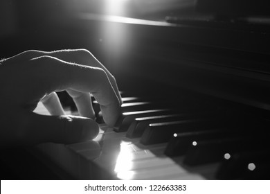 Playing piano - dramatic light, B&W