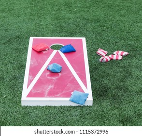 Playing the populare game corn hole on a red and white wood board with blue and red striped bean bags on turf.
