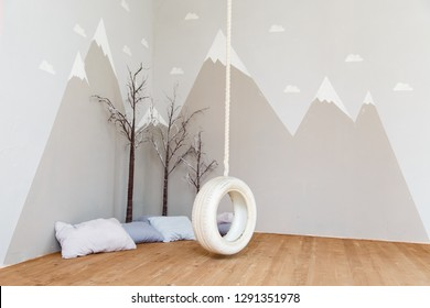 Playing room for a boy. Stylish kid room with illustration of winter mountains and bungee/swing. Mountains illustration in a child room