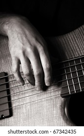 playing six-string electric bass guitar; fingerpicking, right hand; toned monochrome image;