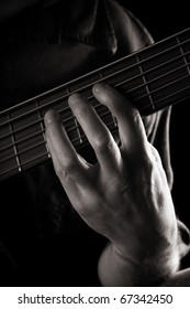 playing six-string electric bass guitar; fretting left hand; toned monochrome image;
