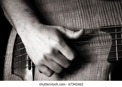 playing six-string electric bass guitar; slap technique; right hand; toned monochrome image;