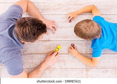 Playing together. Top view of father and son lying on the hardwood floor and playing with toy cars together