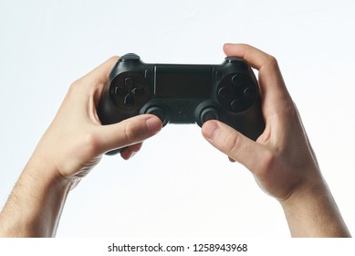 Playing video game theme. Game controller in hands close-up isolated on white background
