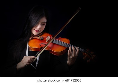 Playing the violin. Musical instrument with hands on dark background.
