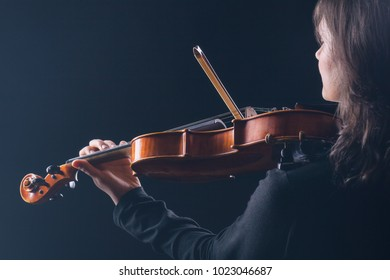 Playing the violin. Woman playing the violin with her back to the camera on a black background