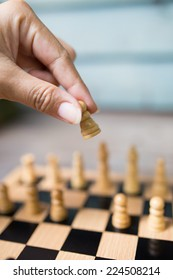 Playing wooden chess, picking the pawn