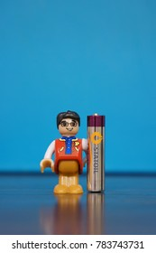 Playtive Junior toy man with glasses holding a Statoil AAA alkaline battery in soft focus on circa December 2017 in Poznan, Poland