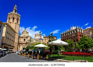 Plaza de la Reina - central place in Valencia, Spain. Lively square surrounded by cafes, bars, shops and historic buildings, with a fountain and shaded benches.