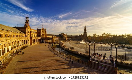Plaza de España in Seville, sunny day with blue sky and white clouds at sunset on a summer day. Golden and orange tones. Andalusia.