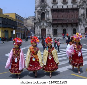 Plaza Mayor, Lima, Peru/8th September 2013/Young beautiful Peruvian women in brightly coloured red festival clothing and multicoloured headresses