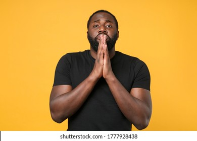 Pleading african american man guy football fan in casual black t-shirt isolated on yellow wall background studio portrait. People lifestyle concept. Mock up copy space. Holding hands folded in prayer