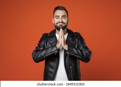Pleading begging young bearded man 20s in basic white t-shirt, black leather jacket standing holding hands folded in prayer looking camera isolated on bright orange colour background, studio portrait