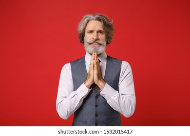 Pleading elderly gray-haired mustache bearded man in classic shirt vest colorful tie posing isolated on red background. People lifestyle concept. Mock up copy space. Holding hands folded in prayer