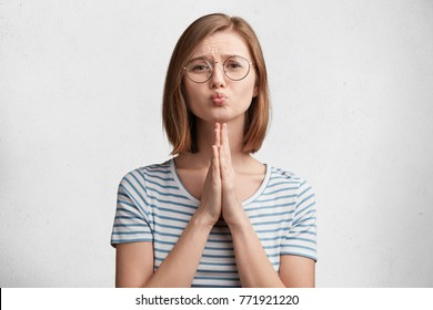 Pleading female student rounds lips and has sorrorful expression asks professor for permission to repass exam, wears round spectacles and striped t shirt, isolated over white concrete background