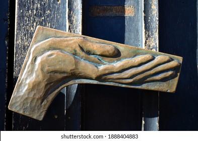 Pleading hand on a church door