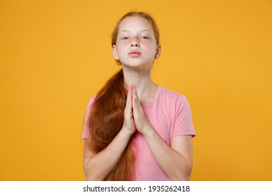 Pleading little ginger redhead kid girl 12-13 years old wearing pink casual t-shirt posing holding hands folded in prayer isolated on bright yellow color wall background children studio portrait