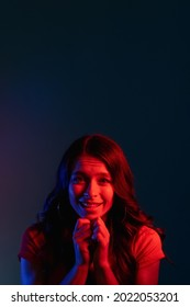 Pleading woman. Asking apology. Request favor. Begging please. Cute smiling young girl with imploring expression in bright red color neon light on dark copy space background.