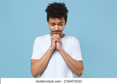 Pleading young african american guy in casual white t-shirt posing isolated on blue background studio portrait. People emotions lifestyle concept. Mock up copy space. Holding hands folded in prayer