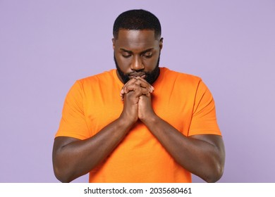 Pleading young african american man wearing basic casual empty blank orange t-shirt standing holding hands folded in prayer looking down isolated on pastel violet colour background studio portrait