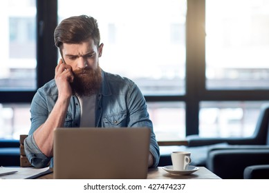 Pleasant bearded man sitting at the table