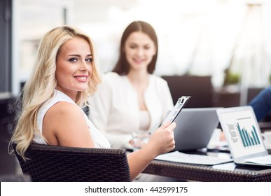 Pleasant beautiful woman sitting at the table